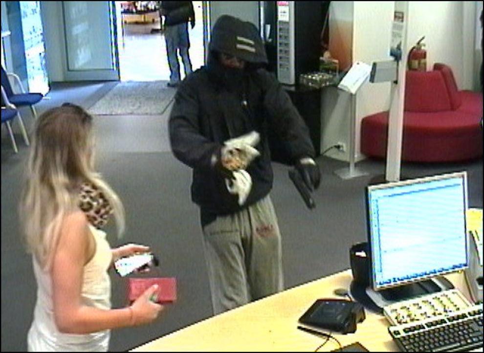 TRUET MED PISTOL: Dette overvåkningsbildet fra SR-banks filial på Kvadrat viser hvordan raneren truer til seg penger med det som ser ut som en pistol. Foto: POLITIET