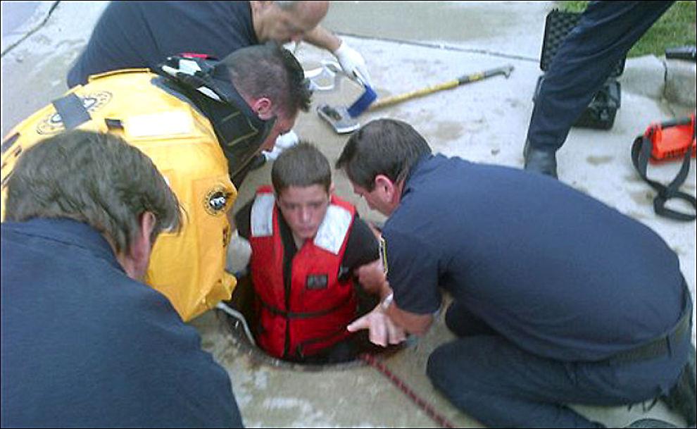 USKADET: 14-åringen blir dratt opp av kloakken 4-500 meter fra stedet han ble sugd inn. Utrolig nok slapp han unna den traumatiske «vannsklie-turen» med bare noen mindre kutt og blåmerker. Foto: AP Photo/Brannvesenet i Parma