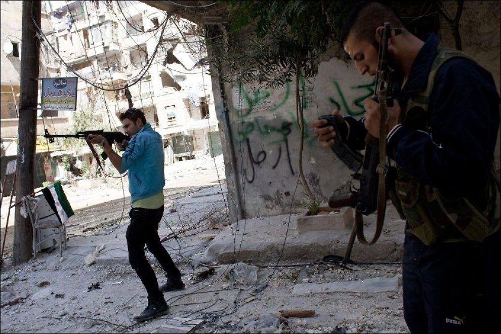 GATEKAMPER: Syriske rebeller deltar i gatekamper i Salaheddin-distriktet i Aleppo 6. september. Kampene om byen har rast siden 20. juli i år. Foto: ACHILLEAS ZAVALLIS / AFP / NTB scanpix