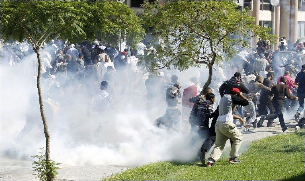 DEMONSTRASJONER FORAN AMBASSADEN I TUNIS: Demonstrantene prøver å søke dekninger mens store sammenstøt foregår utenfor den amerikanskje ambassaden i Tunis. Foto: ZOUBEIR SOUISSI, REUTERS, NTB SCANPIX