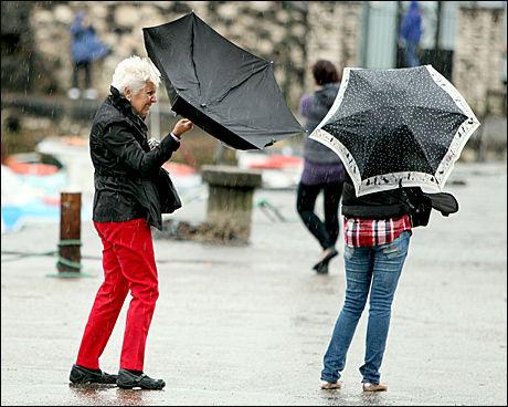PARAPLY-PROBLEMER: Turister i Storbritannia sliter i den kraftige vinden tirsdag formiddag. Foto: PA