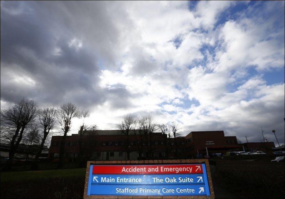 MASSEDØD: Skiltet som står utenfor Stafford sykehus i England peker i retning bygningene hvor flere hundre pasienter skal ha dødd. Pasientene ble liggende i skitt, uten mat og vann, varsler rapporten. FOTO: Darren Stapples, Reuters, NTB Scanpix