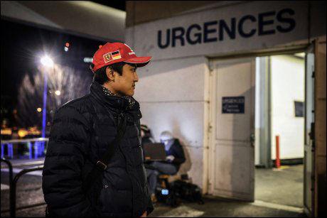 VENTER: En fan av Formel 1-legenden venter på nyheter utenfor sykehuset ikledd den kjente, røde Ferrari-capsen. Foto: Afp