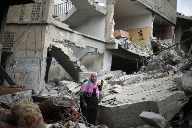 PAUSE: Etter den annonserte våpenhvilen tirsdag benyttet flere palestinere anledningen til å besøke sine hjem. Denne kvinnen går mellom ruinene av huset sitt i Eit Hanoun, nord på Gazastripen.