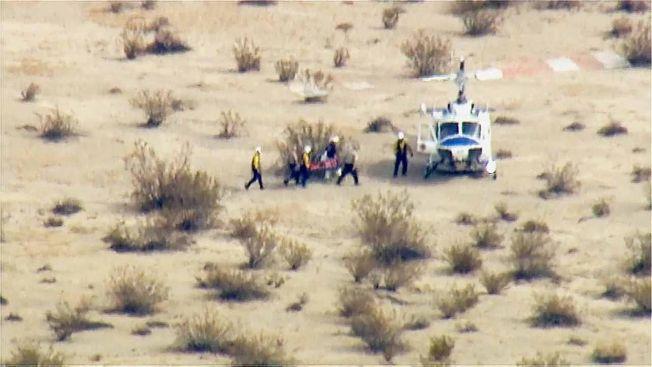 <p>REDNINGSAKSJON: Redningsmannskap bærer en person på båre i Mojave-ørkenen der romflyet styrtet fredag etter testflyvingen. En person er død, og en er alvorlig skadet, ifølge Reuters.<br/></p>