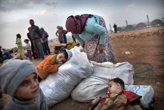 <p>Tusenvis av mennesker flyktet over grensen til Tyrkia da IS angrep Kobani i slutten av september i fjor. Når bor mange av dem på gaten samtidig som det bygges flyktningeleire mange steder i Suruc-provinsen. Hamida Hamelo (30), sammen med barna Saleh (3) i oransje og lille Abian (1,5) sovende er tre av dem. Mannen ble skutt og drept da de flyktet fra Kobani / Kobane og inn i Tyrkia. Nå er hun alenemor for fem barn. Foto: HARALD HENDEN/VG</p>