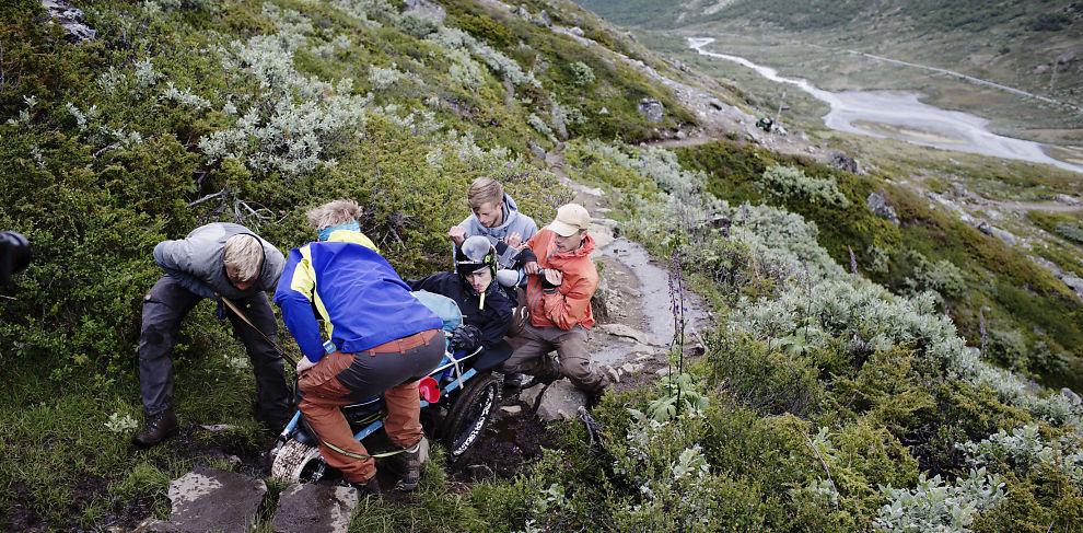 <p>LAGARBEID: Fire personer må trekke Jacobs rullestol opp den bratte stigningen. Turkameratene er fornøyde med kvaliteten på begynnelsen av stien. Her får de til å trille vogna og løfte den over de steinene som er i veien.</p>