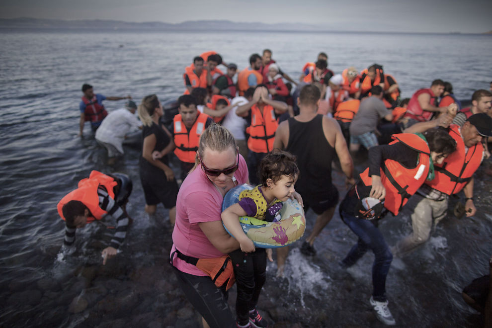<p>En frivillig tar hånd om et lite syrisk barn som har kommet i land med sin familie og andre flyktninger med gummibåt på den greske øya Lesvos tidligere i september. EU vil nå legge til rette for raskere retur av flyktninger fra andre land som ikke kvalifiserer for asyl.</p>