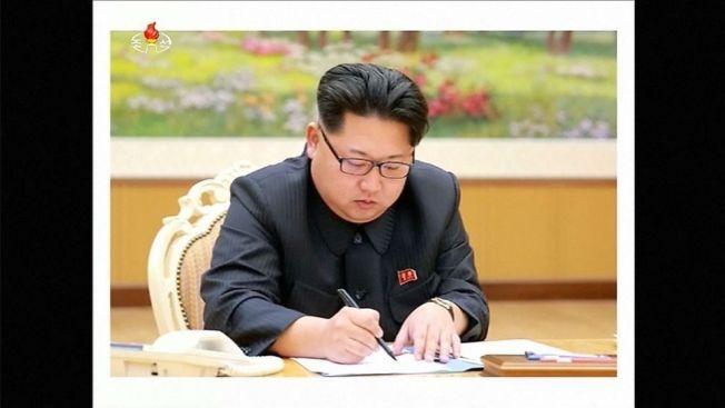 SIGNERTE: Dette stillbildet gitt ut av den statlige TV-kanalen KRT skal angivelig vise Kim Jong-un i det han skriver under sin beordring om å prøvesprenge en hydrogenbombe. Tv-kanalen hevder det er tatt 3. januar i år