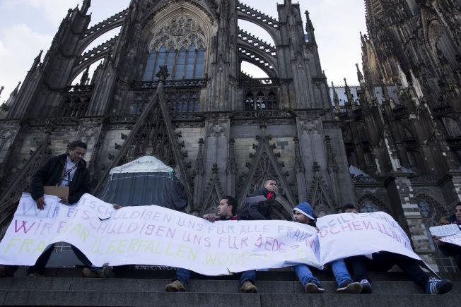 TAR AVSTAND: Flere syriske flyktninger hadde møtt opp ved Kölnerdomen for å vise sin avsky over forbrytelser som kan være begått av andre syrere.