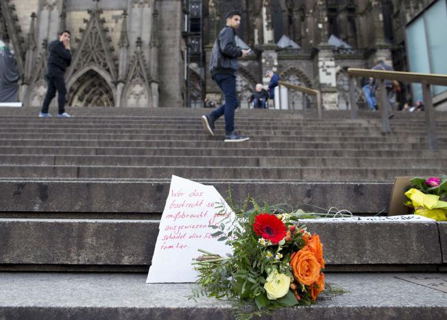"""BLOMSTER: """"Den som misbruker oppholdstillatelsen slik bør utvises, for han skader alle flyktningfamilier"""" står det på kortet på en av blomsterbukettene som er lagt ned på åstedet for masseovergrepene i Köln."""