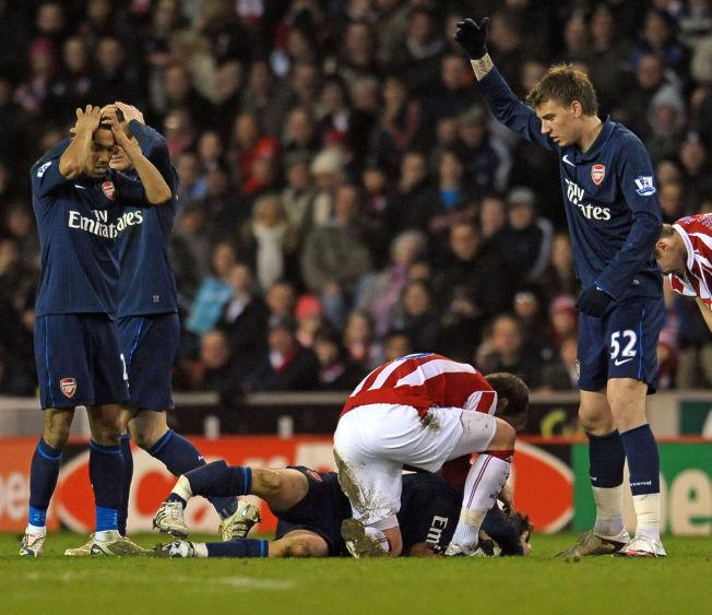 SKREKKSKADE: Stoke-spiller Glenn Whelan (ryggen mot) kommer til for å se til Aaron Ramsey etter han ble taklet av Ryan Shawcross i en kamp i 2010. Flere Arsenal-spillere ser fortvilet på det som har skjedd. Ramsey får likevel gjennomgå av Stoke-fansen.