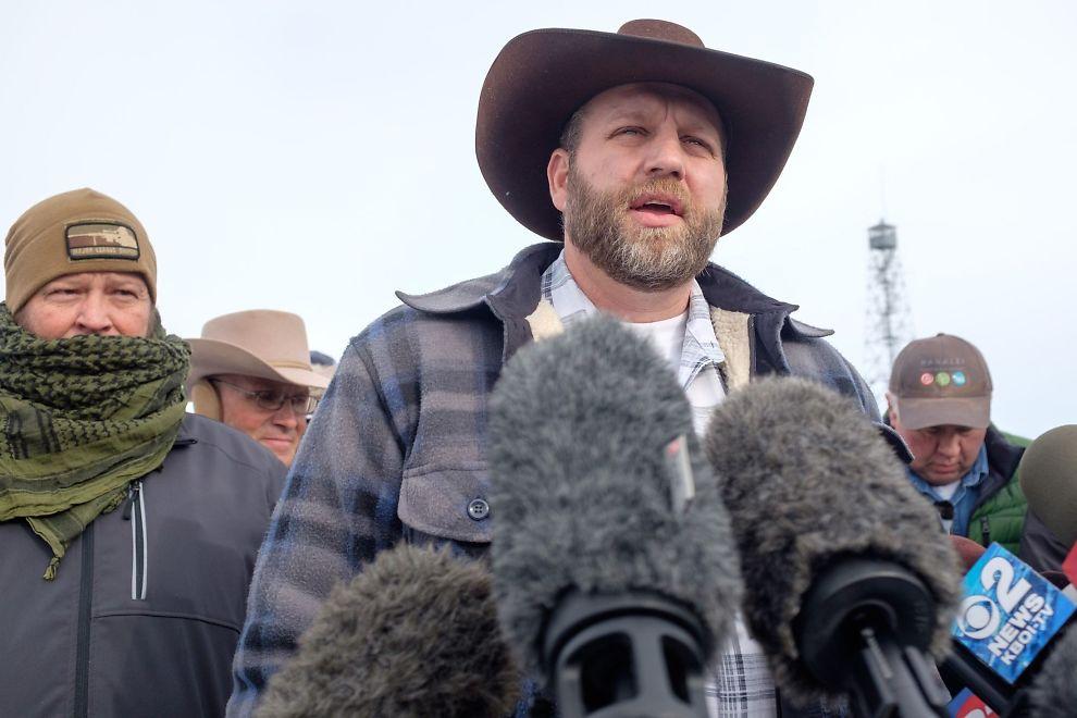 <p>MOT STATLIG KONTROLL: Mannen i cowboyhatt, Ammon Bundy, har flere ganger i løpet av den siste måneden snakket med pressen om hvorfor de tok over bygningen. Her er han 4. januar.</p>