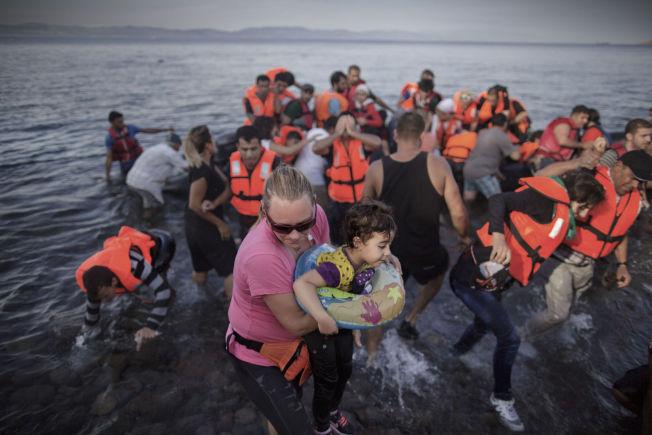 FARLIG REISE: En frivillig tar hånd om et lite syrisk barn som har kommet i land med sin familie og andre flyktninger med gummibåt på den greske øya Lesvos i fjor høst. Flukten over havet er svært farlig.