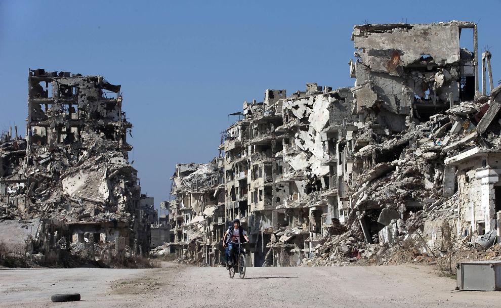 <p>STORE ØDELEGGELSER: En syrisk gutt sykler her gjennom gamlebyen i Homs torsdag.</p>