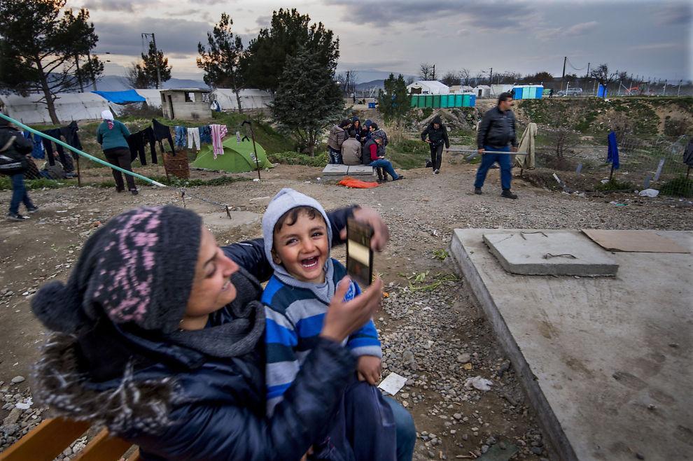 <p>I GRENSELAND: Fra benken i flyktningleiren Idomeni nord i Hellas, holder Karim (2,5) og mamma kontakt med faren i Tyskland via Skype. Hvor lenge de må vente før de får krysse grensen i bakgrunnen og reise nordover, aner de ikke.</p>