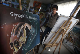 <p>STERKE MINNER: Muhamed el beydum (16), og andre flyktninger lærer å male i Elbeyli flyktningleir.«Virkeligheten i Syria» står det på ett av bildene, som en annen gutt har malt.</p>