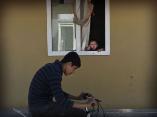 <p>NYTT LIV: En liten gutt titter ut av en av containerne i flyktninggleiren Elbeyli, som ligger på grensen mellom Tyrkia og Syria. Mange har bodd i leiren i tre år, atter andre har flyktet videre til Europa.</p>