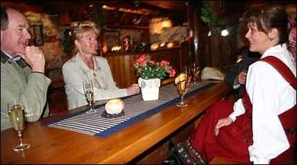 BODEGA-STIL: Den underjordiske vinpuben tar innpå 30 gjester. Her ser vertinne Milly Sivertsen (t.h.) til at Helge Schjølberg og Kirsten Holmen hygger seg.Foto: Dag Fonbæk