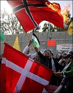 BRANT FLAGG: Palestinske demonstranter i byen Aram på Vestbredden tente på norske og danske flagg i går i protest mot Muhammed-karikaturene. Foto: AP
