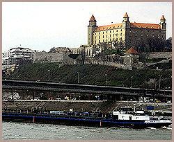DONAU: En lastepram passerer slottet på høyden over Donau. Til venstre for slottet ser du parlamentsbygningen. Foto: AP / Jab Koller