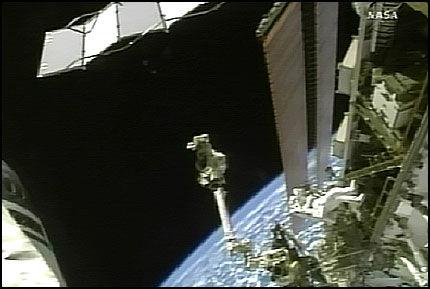I ROMMET: Det første bildet fra romvandringen torsdag kveld. Mens de to astronautene jobbet i rommet, var det en kraftig eksplosjon på Solen. Foto: AP/NASA TV