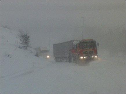 INNESNØDD: Snøen driver tett mellom bilene og vogntogene som har blitt stående maktesløse i snøstormen. Foto: Sondre Aanonsen
