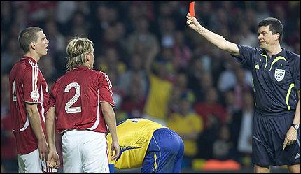 FIKK SOM FORTJENT: Christian Poulsen vises det røde kortet etter at linjemannen snappet opp at han plantet knyttneven i magen på Sveriges Markus Rosenberg. Foto: AFP