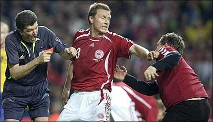 SJOKKET: Dommer Herbert Fandel (t.v.) får hjelp av Michael Gravgaard mot den voldelige danske supporteren som ødela lørdagens kamp. Foto: EPA