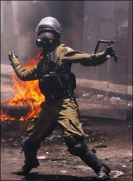 KASTET TILBAKE: Denne politimannen kastet stein tilbake på demonstrantene. Foto: AP
