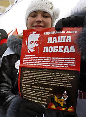 FLYGEBLAD: Et kvinnelig medlem av Nashi holder frem flygebladet hvor det hevdes at «forræderne vil prøve å innta plasser og bygninger, provosere til uro og ta seieren fra oss». Foto: AP