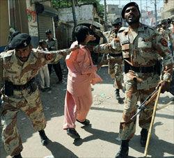 VALGURO: To politimenn arresterer en demonstrant utenfor et valglokale i Karachi. Foto: AFP