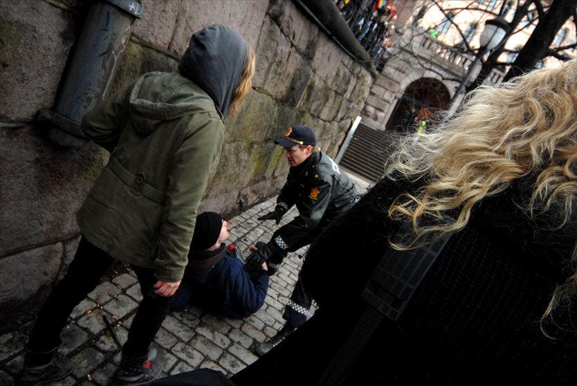 DEMONSTRANT: En demonstrant blir lagt i bakken av politiet etter å ha forsøkt å ta seg opp på scenen. Foto: Aleksander Vallestad