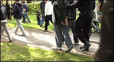 LAGT I JERN: En ung gutt føres bort i håndjern etter å ha nektet å følge politiets ordre til folkemengden om holde avstand til brannen. Foto: Roar Dalmo Moltubak