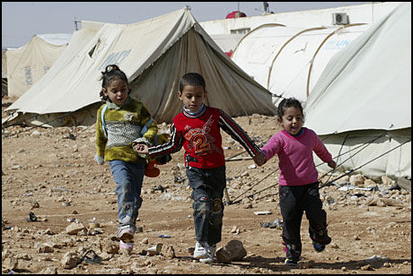 VANSKELIG START: Tre palestinske flyktningbarn leier hverandre gjennom en leir for palestinske flyktninger på grensen mellom Syria og Irak. Rundt 1800 mennesker bor i denne teltleiren, ifølge FNs høykommissær for flyktninger. Foto: REUTERS