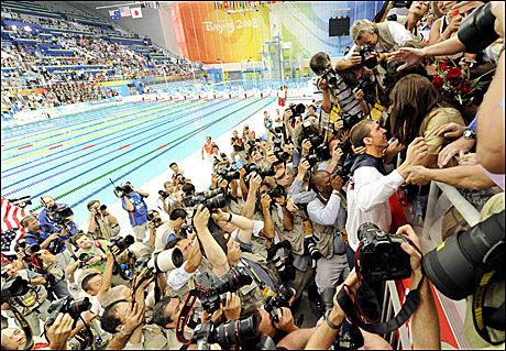 VOLDSOM INTERESSE: Fotografene flokket seg rundt Phelps etter det siste løpet. Foto: EPA