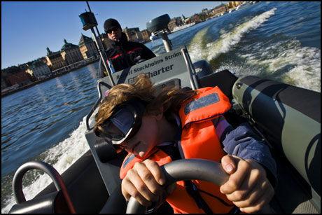 FARTSFYLT: Oliver (6) koser seg, og holder fast i det Mathias Widell gir gass på RIB-båten. Gamla Stan i bakgrunnen forsvinner lenger og lenger bort. Foto: Jan Johannessen