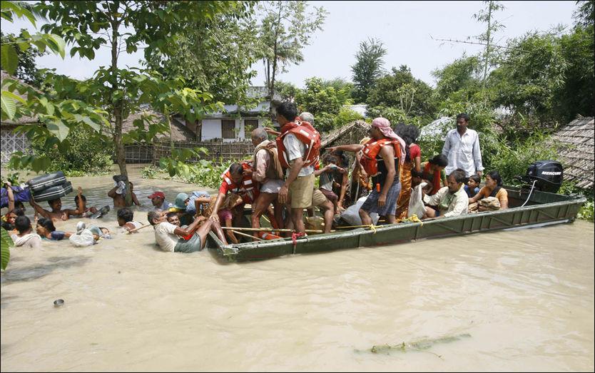 REDDET: Innbyggere i landsbyen Chondipur blir reddet fra oversvømmelsene etter at Kosielven gikk over sine bredder. Foto: Reuters