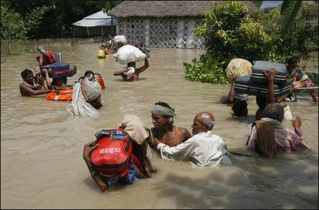 OVERSVØMT: Flomofre i landsbyen Mirchabari bærer det de klarte å få med seg, mens de venter på å bli reddet fra vannmassene. Foto: Reuters