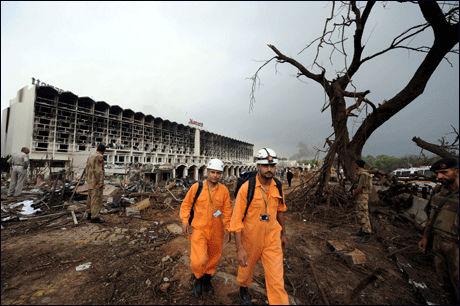 VANSKELIG: Her forlater to redningsarbeidere åstedet, selvmordsaksjonen har paralisert den pakistanske nasjonen. Det har kommet fordømmelser også fra det internasjonale samfunnet Foto: AFP