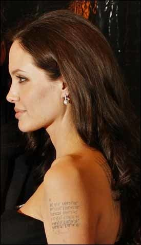 NYE LINJER: De to nederste linjene av tatoveringen på Angelina Jolies venstre overarm viser kordinatene til hvor tvillingene Knox og Vivienne ble født. Foto: REUTERS