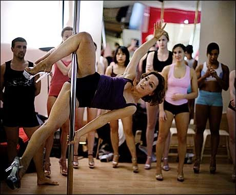 AKROBATISK: Teaterlærer, intruktør og skuespiller Mariana Baum viser elevene ved Pole-Dance Paris hvordan de skal skli horisontalt ned stangen. Foto: Jørgen Braastad