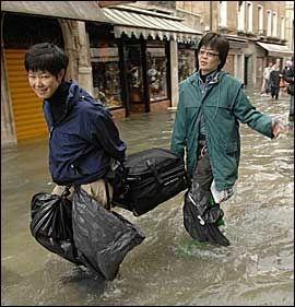 RØMMER: Disse turistene forlot Venezia og de store vannemengdene i dag. Foto: Reuters