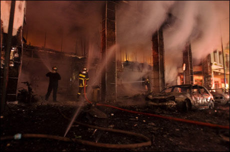 UTBRENT: Brannvesenet forsøker å slukke brannen i en butikk i Athen. Over hele den greske hovedstaden har det i natt vært opptøyer etter at en 16 år gammel gutt ble skutt og drept av politiet. Foto: AP