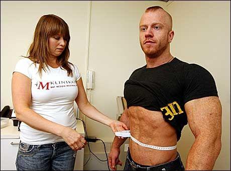 STERK, IKKE TYKK: Bjørgulf Hansen ble nummer fire i Mister Universe, men er overvektig ifølge BMI. Men Bjørgulf har bare en fettprosent på 7,7. Lege Katarina Lien sjekker her livvidden hans. - Livvidden og fettprosenten betyr mer enn BMI, fordi muskler veier mer enn fett, sier Lien. Foto: Trond Solberg