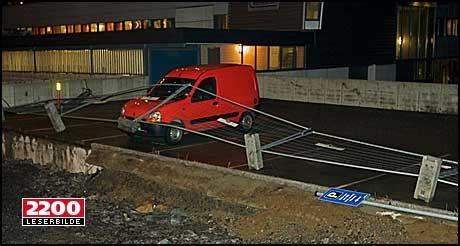 BLÅST GODT: En bil har fått et sperregjerde for et anleggsområde over seg i Bodø. Legg også merke til skiltet nede til høyre; hele sementstøtta gikk over ende. Det har blåst godt i Nordland over natta. Foto: Leserbilde