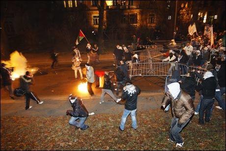 KASTET STEIN: Demonstranter kastet stein mot politiet utenfor den israelske ambassaden i Oslo mandag kveld. Politiet svarte med tåregass. Foto: Reuters