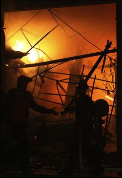 UNDER ANGREP: Brannmenn jobber med slukningsarbeid i en palestinsk butikk etter et rakettangrep lørdag. Lørdag kveld gikk bakkestyrker inn i Gaza. Foto: AP