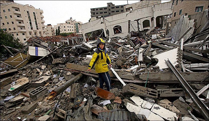 FORTSETTER: Israel fortsetter rakettangrepene på Gazastripen, en ny Hamas-topp er blitt drept under nattens angrep. På bildet ser man en palestinsk gutt i Gaza som ser på ødeleggelsene etter et angrep. Foto: EPA