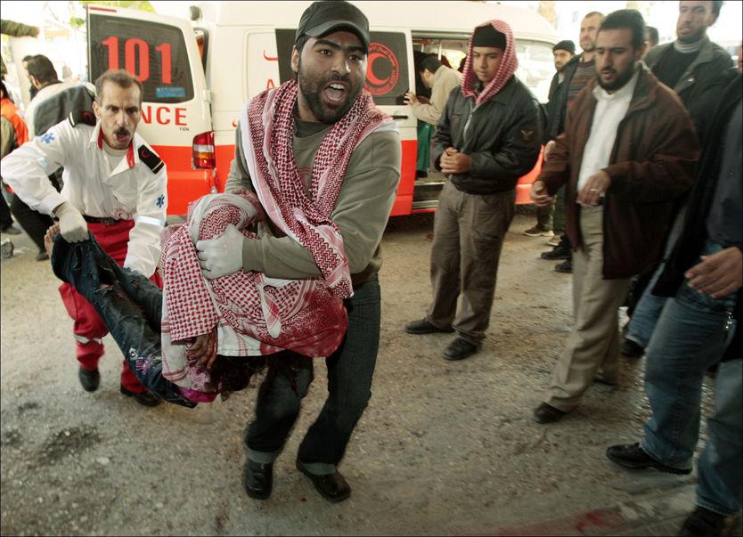 BARN SPARES IKKE: Et skadet barn blir brakt ut fra ambulansen etter et granatangrep i Gaza. Nå flykter kvinner og barn fra den blodige krigen, som rammer alle. Foto: Reuters
